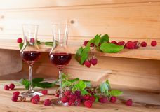Two glasses of raspberry liqueur with ripe berries . Two glasses of raspberry liqueur with ripe berries on wooden background Royalty Free Stock Photo