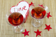 Two glasses with a red alcoholic drink and heart shaped candles Stock Photography