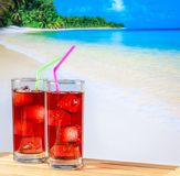 Two glasses of red cocktail with blur beach and space for text Stock Photography