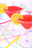 Two glasses with red cocktail vertical. Two glasses with red cocktail and yellow lemon slices on a light background. Cocktail tubes on background.  view from Stock Photos