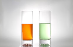 Two glasses red and green. Two glasses with red and green liquids royalty free stock photography