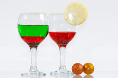 The two glasses of red and green liquo. The two glasses of transparent red and green liquor and lemon Stock Image