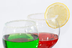 The two glasses of red and green liquor. The two glasses of transparent red and green liquor and lemon Stock Images