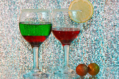 Two glasses of red and green liquor and lemon. The two glasses of transparent red and green liquor and lemon Stock Image
