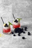 Two glasses of red juice and white ice, drinking straws, green mint, blackberries on a light gray background. A gray table with sappy blackberries, two glasses Stock Images