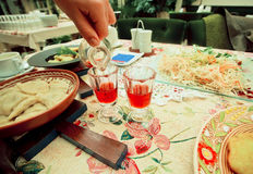 Two glasses with red liqueur on the rich restaurant table Stock Photos