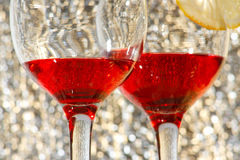 Two glasses of red liquor and lemon. The two glasses of transparent red liquor and lemon Stock Photos