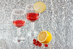 Two glasses of red liquor, lemon and raspberries. The two glasses of transparent red liquor, lemon and raspberries Royalty Free Stock Photography