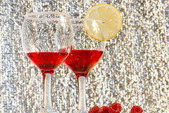 Two glasses of red liquor, lemon and raspberries. The two glasses of transparent red liquor, lemon and raspberries Royalty Free Stock Image
