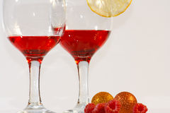 Two glasses of red liquor, lemon and raspberries. The two glasses of transparent red liquor, lemon and raspberries Royalty Free Stock Photo