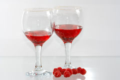 The two glasses of red liquor and rasp. The two glasses of transparent red liquor and raspberries Stock Photography