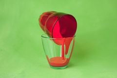 Two glasses with red paint on a green background Royalty Free Stock Images