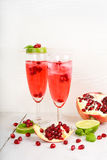 Two glasses with red pomgranate champagne, lime and mint. royalty free stock photo