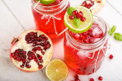 Two glasses with red pomgranate juice, lime and mint. Royalty Free Stock Photography