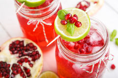 Two glasses with red pomgranate juice, lime and mint. Stock Photo