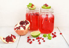 Two glasses with red pomgranate juice, lime and mint. Royalty Free Stock Photos