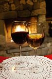 Two glasses of red white wine, fireplace chimney background. romantic xmas postcard, cozy interior of a xmas evening. Two glasses of red white wine, fireplace stock images