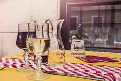 Two glasses of red and white wine served on a table in an traditional italian restaurant. Two glasses of red and white wine served on a table in an traditional stock images