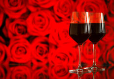Two glasses of red wine against bokeh background with sparkles and roses. Very shallow depth of field. Stock Photo