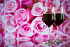 Two glasses of red wine against bokeh background with sparkles and roses. Very shallow depth of field. Stock Image