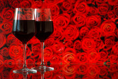 Two glasses of red wine against bokeh background with sparkles and roses. Very shallow depth of field. Royalty Free Stock Photography