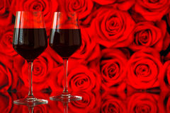 Two glasses of red wine against bokeh background with sparkles and roses. Very shallow depth of field. Royalty Free Stock Images
