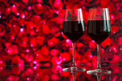 Two glasses of red wine against bokeh background with sparkles and roses. Very shallow depth of field. Stock Photos
