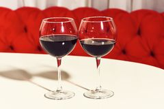 Two glasses of red wine, alcoholic drink, beverage, served on white table in cafe or bar on sofa background. stock images