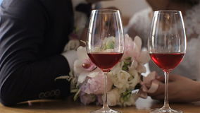 Two glasses of red wine on a background of beautiful wedding couple. Slow motion stock video footage
