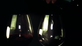 Two glasses of red wine being poured. Two glasses and bottle of red wine. Wine is poured into glasses. Black background. Close-up stock footage