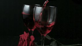 Two glasses of red wine being poured with red rose. On black background stock video footage