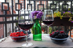 Two glasses of red wine with berries and violets at serbian terrace with city view Stock Images