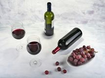 Two glasses of red wine with bottle and grapes. Stock Images