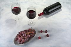 Two glasses of red wine with bottle and grapes. Two glasses of red wine with bottle and grapes Stock Photography