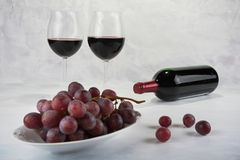 Two glasses of red wine with bottle and grapes. Royalty Free Stock Images