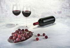 Two glasses of red wine with bottle and grapes. Stock Photo