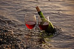 Two Glasses Red Wine and Bottle in Ocean. This is a photo of 2 glasses of red wine and the wine bottle at the shore of a beach with waves Royalty Free Stock Photos