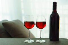 Two glasses of red wine and a bottle Stock Images
