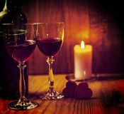 Two glasses of wine with lcandle in the background. Two glasses of red wine with a bottle on wooden table with rcandle in the background Stock Image