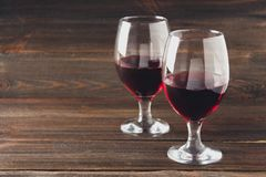 Two glasses of red wine on a brown wooden table. Alcoholic beverages. Two glasses of red wine on a brown wooden table. Alcoholic beverages Stock Image