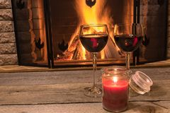 Two glasses of red wine and candle near cozy fireplace, in country house, winter vacation, horizontal. Tranquil scene before cozy fireplace, with two glasses of stock images