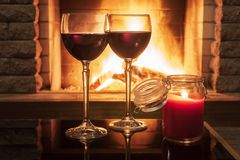 Two glasses of red wine and candle near cozy fireplace, in country house, winter vacation, horizontal. Tranquil scene before cozy fireplace, with two glasses of stock photography