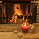 Two glasses of red wine and candles near cozy fireplace, in country house, winter vacation, horizontal. Tranquil scene before cozy fireplace, with two glasses of stock photography
