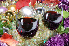 Two glasses of red wine on a Christmas background. With tinsel and baubles royalty free stock photos