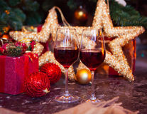 Two glasses of red wine on a Christmas tree background Royalty Free Stock Image