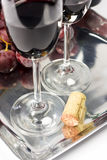 Two glasses of red wine with cork. Glasses of red wine with grapes and cork sitting nearby Stock Image