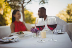 Two glasses of red wine with couple in background Royalty Free Stock Photography