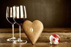 Two glasses of red wine, gingerbread and christmas baubel Royalty Free Stock Image