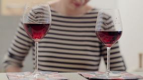 Two glasses of red wine and girl in a striped T-shirt in the background. Two glasses of red wine. Girl in a striped T-shirt in the background stock video footage