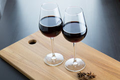 Two glasses with red wine. Two glases with red wine and three anise stars on wood surface Stock Photo